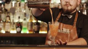 Il colpo vicino alle mani del ` s del barista, un uomo versa un cocktail da un agitatore in un vetro video d archivio