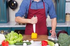Il coltello ceramico a disposizione ha tagliato la verdura gialla del pepe a bordo Immagine Stock