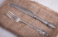 Il coltello d'argento d'annata e la forcella delle stoviglie è sul tovagliolo, su un vecchio Fotografia Stock Libera da Diritti