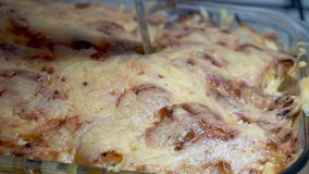 Il coltello taglia le lasagne al forno cucinate a casa Alimento casalingo archivi video