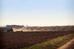 il coltivatore alza la polvere sul campo arato vicino alla strada a terra Immagini Stock
