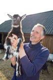 Il coltivatore con goatling. fotografia stock libera da diritti