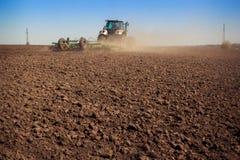 il coltivatore del trattore alza la grande polvere su suolo Fotografie Stock
