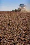 il coltivatore del trattore alza la grande polvere su suolo Immagini Stock