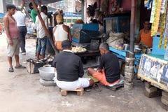 Il commerciante della via vende gli alimenti a rapida preparazione per la gente affamata sulla strada affollata in Calcutta fotografia stock