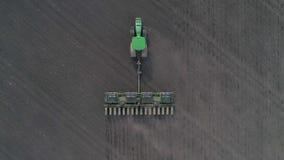 Il commercio nel settore agricolo, metraggio aereo del trattore moderno tratta la terra nel campo facendo uso degli aratri alla m archivi video