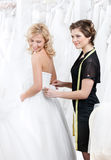 Il commesso contribuisce alla sposa a mettere il vestito sopra Immagine Stock