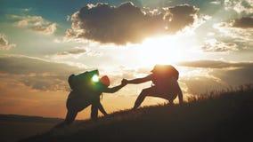 Il compagno di squadra d'aiuto dello scalatore scalare, l'uomo con lo zaino ha raggiunto fuori una mano amica al suo amico Amico  stock footage