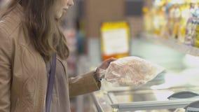 Il compratore adorabile della ragazza sceglie il manzo congelato nel congelatore archivi video