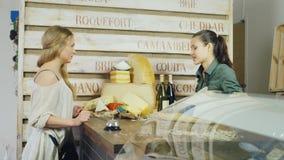 Il compratore comunica con il venditore in una piccola drogheria Frigorifero-vetrina vicina con i prodotti stock footage