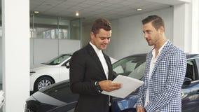 Il compratore ed il venditore potenziali hanno letto le caratteristiche dell'automobile fotografie stock libere da diritti