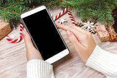 Il compratore femminile fa l'ordine allo schermo dello smartphone con lo spazio della copia Vendite di vacanze invernali Acquisto Immagine Stock