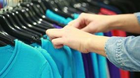 Il compratore sceglie una maglietta in un boutique video d archivio
