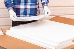 Il compratore si raccoglie pronto--monta il tavolo pieghevole Pronto--monti la mobilia Il lavoratore apre la scatola con mobilia fotografia stock libera da diritti
