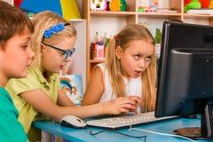 Il computer dei bambini ci classifica per istruzione ed il video gioco Immagine Stock