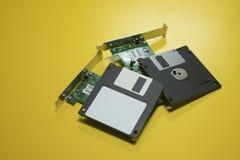 Il computer magnetico a disco magnetico ed il circuito elettronico hanno messo sopra un fondo giallo dello scrittorio Fuoco selet Immagini Stock Libere da Diritti