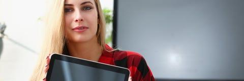 Il computer portatile abbastanza biondo della tenuta della giovane donna in armi si siede sul sofà Fotografie Stock Libere da Diritti