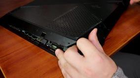 Il computer portatile, ha rimosso la copertura posteriore, i chip visibili e la mano di un padrone Il concetto dei computer porta stock footage