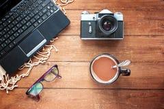 Il computer portatile, tazza di caffè, la macchina fotografica e punti su una linguetta di legno Fotografie Stock