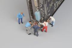Il computer ripara il concetto con le mini figure e componenti Immagini Stock