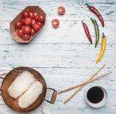 Il concetto che cucina Funchoza con peperoncino, pomodori e salsa di soia, ha allineato con una struttura su fondo di legno rusti Fotografie Stock Libere da Diritti