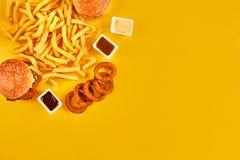 Il concetto degli alimenti a rapida preparazione con il ristorante fritto grasso elimina come gli anelli di cipolla, l'hamburger, Immagine Stock Libera da Diritti