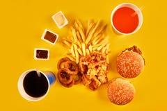 Il concetto degli alimenti a rapida preparazione con il ristorante fritto grasso elimina come gli anelli di cipolla, l'hamburger, Fotografia Stock