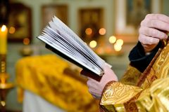 Il concetto dei sacramenti della chiesa - battesimo, nozze, Pasqua, resurrezione Libro di preghiera nelle mani di un sacerdote or fotografia stock