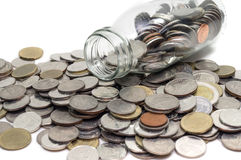 Il concetto dei soldi di risparmio di raccolta conia nell'isolato della bottiglia di vetro Fotografia Stock