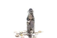 Il concetto dei soldi di risparmio di raccolta conia nell'isolato della bottiglia di vetro Immagine Stock
