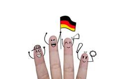 Il concetto del dito incoraggia sul gruppo che il calcio con sostiene la bandiera Germania Immagini Stock