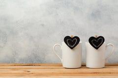 Il concetto del giorno di biglietti di S. Valentino con le tazze di caffè ed il cuore della lavagna modella Fotografia Stock