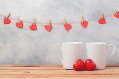 Il concetto del giorno di biglietti di S. Valentino con le tazze ed il cuore di caffè macchiato modella sopra fondo rustico Immagine Stock