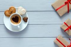 Il concetto del giorno di biglietti di S. Valentino ha avvolto il caffè dei regali con le caramelle su legno Fotografia Stock