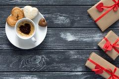 Il concetto del giorno di biglietti di S. Valentino ha avvolto il caffè dei regali con le caramelle su legno Immagini Stock