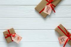 Il concetto del giorno di biglietti di S. Valentino ha decorato i contenitori di regalo su legno bianco Immagine Stock