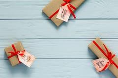 Il concetto del giorno di biglietti di S. Valentino ha decorato i contenitori di regalo su legno grigio Fotografia Stock