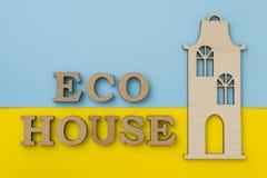 Il concetto dell'alloggio di eco Esprima la casa di eco, con fondo blu giallo, modello di legno della casa Immagine Stock Libera da Diritti