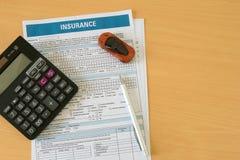 Il concetto dell'assicurazione auto ha creato usando la forma di assicurazione con l'automobile, il calcolatore e la penna miniat fotografia stock