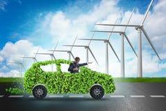 Il concetto dell'automobile elettrica con i mulini a vento Fotografia Stock Libera da Diritti
