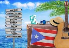 Il concetto dell'estate che viaggiano con la vecchia valigia e la città del Porto Rico firmano Fotografia Stock Libera da Diritti