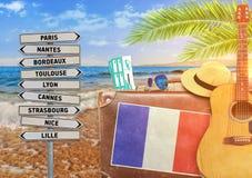 Il concetto dell'estate che viaggiano con la vecchia valigia e la città della Francia firmano Immagini Stock