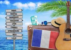 Il concetto dell'estate che viaggiano con la vecchia valigia e la città della Francia firmano Fotografie Stock