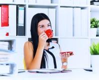 Il concetto della pausa caffè, donna di affari beve il caffè preparato istante mentre lavora con una pila di carte che si siedono immagini stock libere da diritti