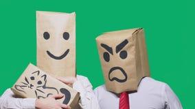 Il concetto delle emozioni e dei gesti Due persone in sacchi di carta con gli smiley Lo smiley aggressivo giura  immagini stock libere da diritti