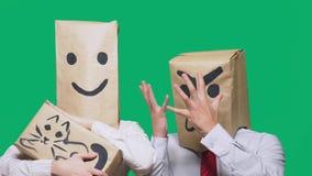 Il concetto delle emozioni e dei gesti Due persone in sacchi di carta con gli smiley Lo smiley aggressivo giura  fotografie stock
