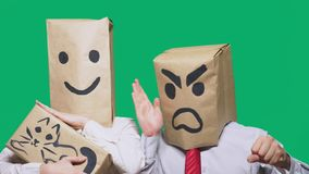 Il concetto delle emozioni e dei gesti Due persone in sacchi di carta con gli smiley Lo smiley aggressivo giura  fotografie stock libere da diritti