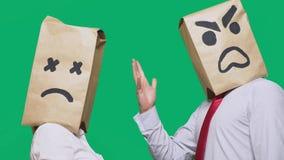 Il concetto delle emozioni e dei gesti Due persone in sacchi di carta con gli smiley Lo smiley aggressivo giura Il secondo immagine stock