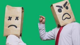 Il concetto delle emozioni e dei gesti Due persone in sacchi di carta con gli smiley Lo smiley aggressivo giura Il secondo fotografie stock libere da diritti
