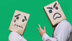Il concetto delle emozioni e dei gesti Due persone in sacchi di carta con gli smiley Lo smiley aggressivo giura Secondo gridare immagine stock libera da diritti